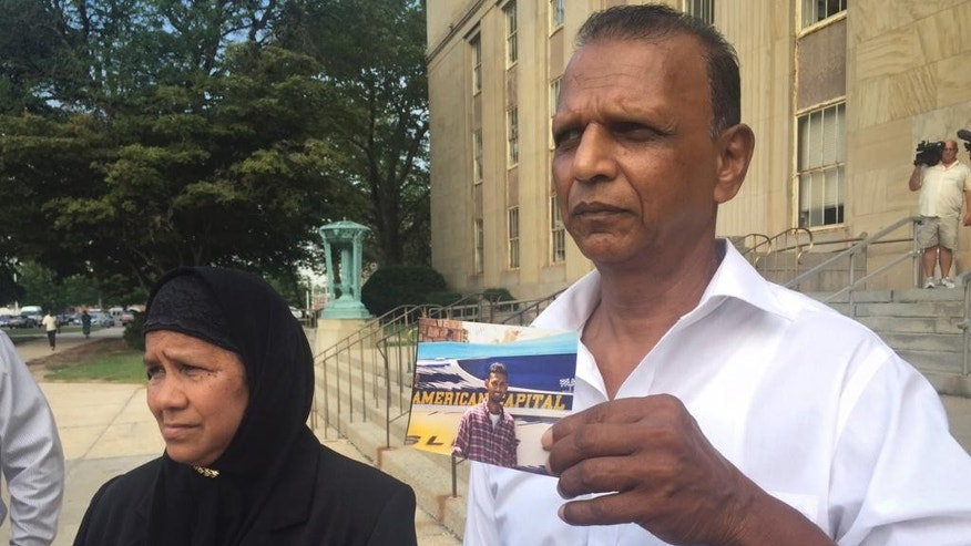 Sharifan Khan, left, stands with her husband Ishanallie Khan, right, as he shows a photo of their son Abzal Khan outside Nassau County Court, Monday, Aug. 17, 2015, in Mineola, N.Y. The Khan's attended court for the arraignment of Balkumar Singh, who was arrested in Trinidad this year after 16 years on the run on charges related to the fatal shooting of Abzal outside a New York wedding in 1999. (AP Photo/Michael Balsamo)