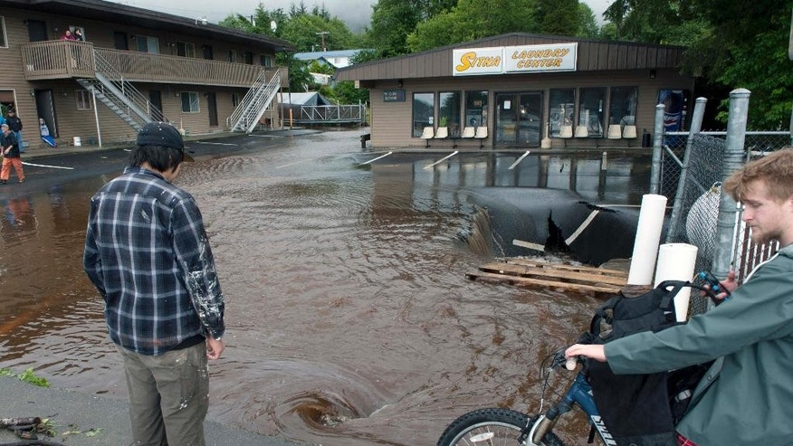 Pedestrians look at the flood damaged Sitka Laundry Center parking lot on Halibut Point Road, Tuesday, Aug. 18, 2015 in Sitka, Alaska. Homes in the town have been flooded, and there were reports of residents not being able to reach their homes or leave their neighborhood, said a spokesman for the state Department of Homeland Security and Emergency Management. (James Poulson/The Daily Sitka Sentinel via AP) MANDATORY CREDIT