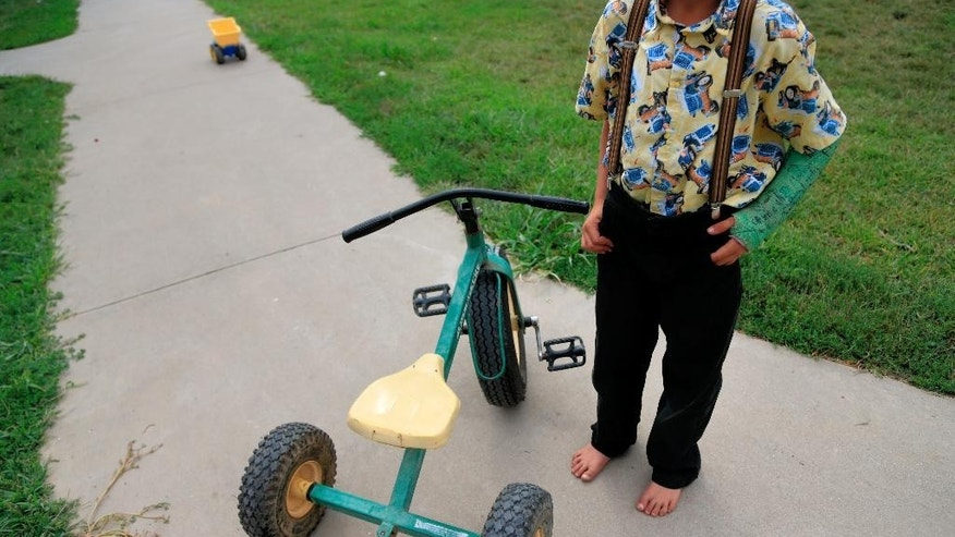 A young Hutterite poses with his tricycle at the Tschetter Colony near Olivet, S.D., Thursday, Aug. 13, 2015. The Hutterites, a deeply religious people, who live in insular farming communities in the Plains, Upper Midwest and Canada, prefer not to have their faces photographed. Nurse Kerri Lutjens has spent the past few years gaining the trust of several communities of Hutterites. (AP Photo/Nati Harnik)