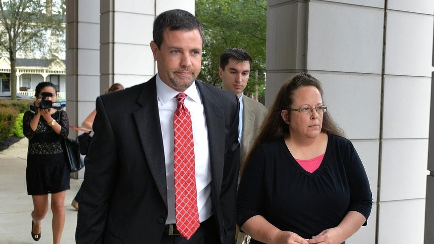 FILE - In this July 20, 2015 file photo, Rowan County Clerk Kim Davis, right, walks with her attorney Roger Gannam into the United States District Court for the Eastern District of Kentucky in Covington, Ky. The Rowan County, Ky., clerk's office turned away gay couples who sought marriage licenses on Thursday, Aug. 13, 2015, defying a federal judge's order that said deeply held Christian beliefs don't excuse officials from following the law. The fight in Rowan County began soon after the Supreme Court legalized gay marriage nationwide in June. Davis cited her religious beliefs and decided not to issue marriage licenses to any couple, gay or straight. (AP Photo/Timothy D. Easley, File)