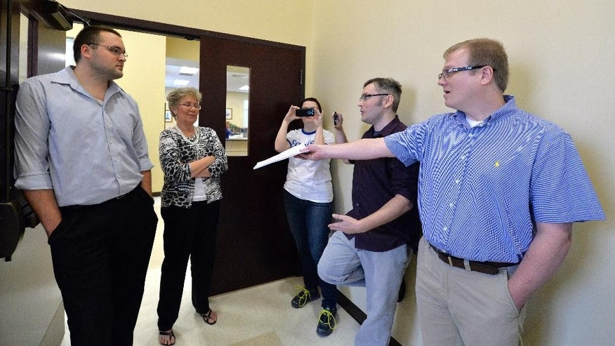 David Ermold, right, attempts to hand Rowan County clerks Nathan Davis, left, and Roberta Earley, second from left, a copy of the ruling from U.S. District Court Judge David Bunning, instructing the county to start issuing marriage licenses, in Morehead, Ky., Thursday, Aug. 13, 2015. Rowan County Clerk Kim Davis has refused the order and has filed an appeal. (AP Photo/Timothy D. Easley)