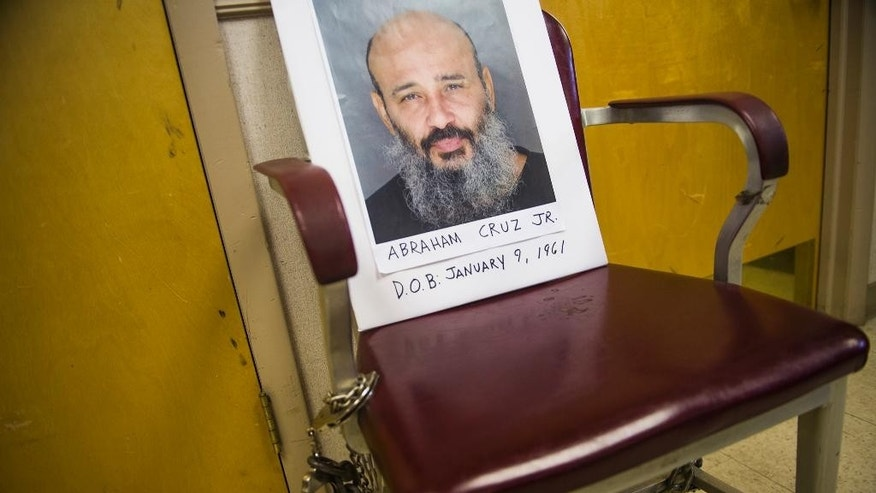 Prosecutors display a photograph of Abraham Cruz Jr. during a news conference, Tuesday, Aug. 18, 2015, at the Pennsylvania State Police barracks in Gettysburg, Pa., as they annoucned two counts of criminal homicide filed against the 54-year-old Cruz in connection with the Aug. 30, 1980, deaths of a mother and her daughter. Prosecutors say Cruz shot and killed 17-year-old Deborah Patterson and her mother, Nancy Patterson, during an early morning burglary at their home in Freedom Township, Adams County, near Gettysburg. (Shane Dunlap/The Evening Sun via AP) MANDATORY CREDIT