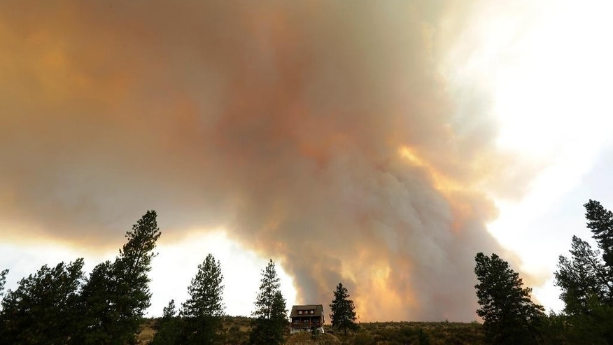 Smoke from an approaching wildfire looms over a home near Twisp, Wash., Wednesday, Aug. 19, 2015. Authorities on Wednesday afternoon urged people in the north-central Washington town to evacuate because of a fast-moving wildfire. (AP Photo/Ted S. Warren)