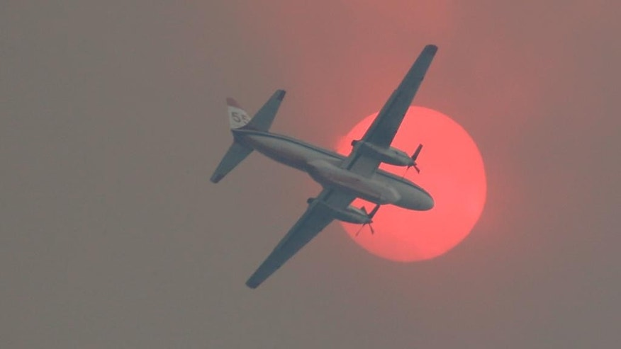 A fire-retardant airplane passes in front of the sun turned orange with smoke as a wildfire burns near Twisp, Wash. Wednesday, Aug. 19, 2015. (AP Photo/Ted S. Warren)
