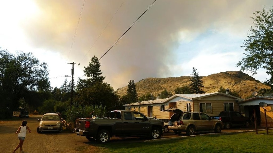 Smoke rises from a wildfire approaching Twisp, Wash., Wednesday, Aug. 19, 2015. Authorities on Wednesday afternoon urged people in the north-central Washington town to evacuate because of a fast-moving wildfire. (AP Photo/Ted S. Warren)