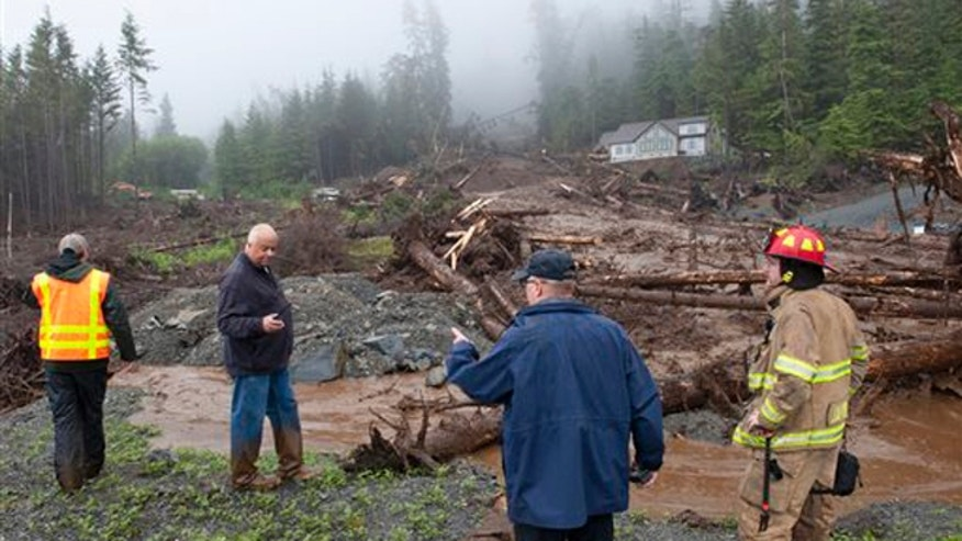 Aug. 18, 2015: From left, city engineer Dan Tadic, Fire Chief Dave Miller, Search and Rescue Capt. Lance Ewers, and firefighter Rob Janik look at the damage caused by a landslide on Kramer Drive in SItka, Alaska.
