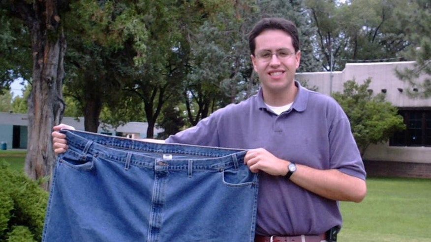 FILE - In this Aug. 7, 2001 file photo, Jared Fogle holds up a pair of jeans he used to wear after losing weight in Albuquerque, N.M.   Subway benefited hugely from  Fogle's weight loss story. Now the sandwich chain needs to figure out how to prevent him from overshadowing its future. (AP Photo/Ivan Chavez)