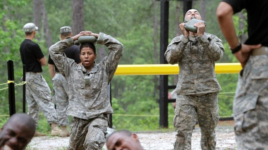 In this photo taken on April 19, 2015, one of the 20 female soldiers, top left, who is among the 400 students who qualified to begin Ranger School, does lunges in between obstacles on the Darby Queen, one of the toughest obstacle courses in U.S. Army training, at Fort Benning, Ga. Two women have passed the Army's grueling Ranger test, but tougher and more dangerous jobs could lie ahead, senior officials told The Associated Press. The military services are poised to allow women to serve in most front-line combat jobs, including as special operations forces.  (Robin Trimarchi/Ledger-Enquirer via AP) MANDATORY CREDIT