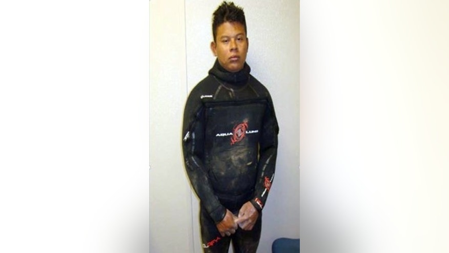 This April 25, 2015 photo, from the U.S. Border Patrol and introduced as evidence in U.S. District Court, shows Evelio Padilla, a Honduran national, in a wetsuit after his arrest for attempting to smuggle over 50 pounds of cocaine into the U.S. from Mexico by way of a partly-underwater tunnel that crossed the border into a canal near Calexico, Calif. (U.S. Border Patrol via AP)