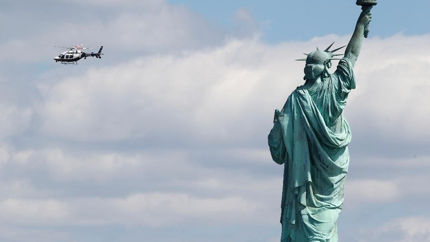 "FILE - In this April 24, 2015 file photo, a New York Police helicopter circles over Liberty Island where the Statue of Liberty was evacuated with officers responding to a report of a suspicious package seen from Jersey City, N.J., Federal authorities say they've arrested a man for making the hoax bomb threat to ""blow up"" the Statue of Liberty in April, resulting in an evacuation of Liberty Island. They say the West Virginia man has held in Texas. A complaint filed Wednesday, Aug. 19, 2015, in federal court in New York says John Paul Smith identified himself as Abdul Yasin when he called 911 from his iPad on April 24. Yasin is the only conspirator not captured in the 1993 World Trade Center bombing. (AP Photo/Julio Cortez, File)"