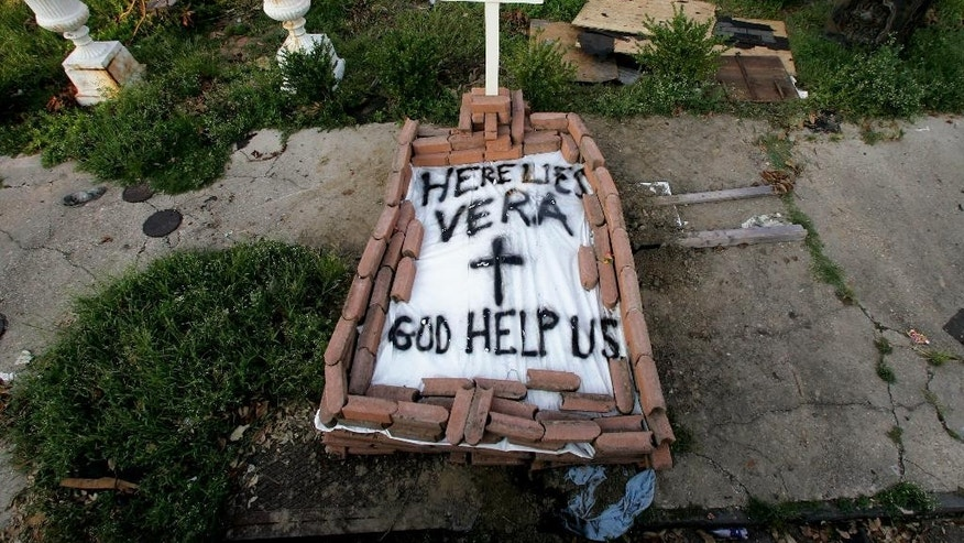"FILE - In this Sept. 4, 2005, file photo, a makeshift tomb at a New Orleans street corner conceals a body that had been lying on the sidewalk for days in the wake of Hurricane Katrina. The message reads, ""Here lies Vera. God help us."" Smith's cremated remains were later reburied in Texas, yet she remains part of her old community. (AP Photo/Dave Martin, File)"
