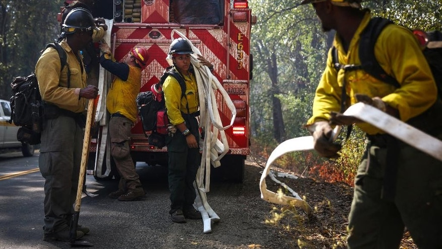Firefighters prepare near an area where fire erupted in Twisp, Wash., Thursday, Aug. 20, 2015. Authorities warned that more high winds Thursday could make conditions very challenging. (Joshua Trujillo/seattlepi.com via AP) MAGS OUT; NO SALES; SEATTLE TIMES OUT; TV OUT; MANDATORY CREDIT; SEATTLE OUT