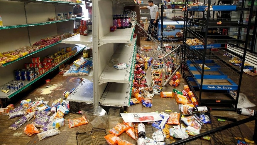 Adam's Market owner Sanad Motan stands inside his ransacked store, Thursday, Aug. 20, 2015, in St. Louis. The store is near where officers arrested several people and deployed tear gas amid protests in St. Louis following the death of a black 18-year-old who was fatally shot by police Wednesday after he allegedly pointed a gun at them while attempting to serve a search warrant in a crime-troubled section of the city's north side. (AP Photo/Jeff Roberson)