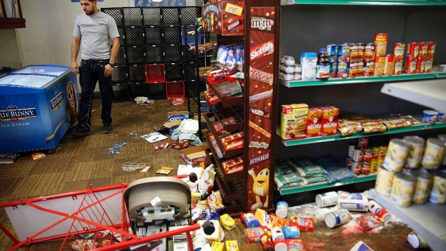 Adam's Market owner Sanad Motan stands inside his ransacked store Thursday, Aug. 20, 2015, in St. Louis. The store is near where officers arrested several people and deployed tear gas amid protests in St. Louis following the death of a black 18-year-old who was fatally shot by police Wednesday after he allegedly pointed a gun at them while attempting to serve a search warrant in a crime-troubled section of the city's north side. (AP Photo/Jeff Roberson)