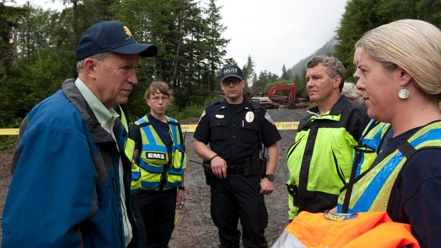 Alaska Gov. Bill Walker, left, talks with emergency workers at the landslide site on Kramer Ave. in Sitka, Alaska, Wednesday, Aug. 19,  2015. Three men missing in the slide were being searched for Wednesday. (James Poulson/Daily Sitka Sentinel via AP)