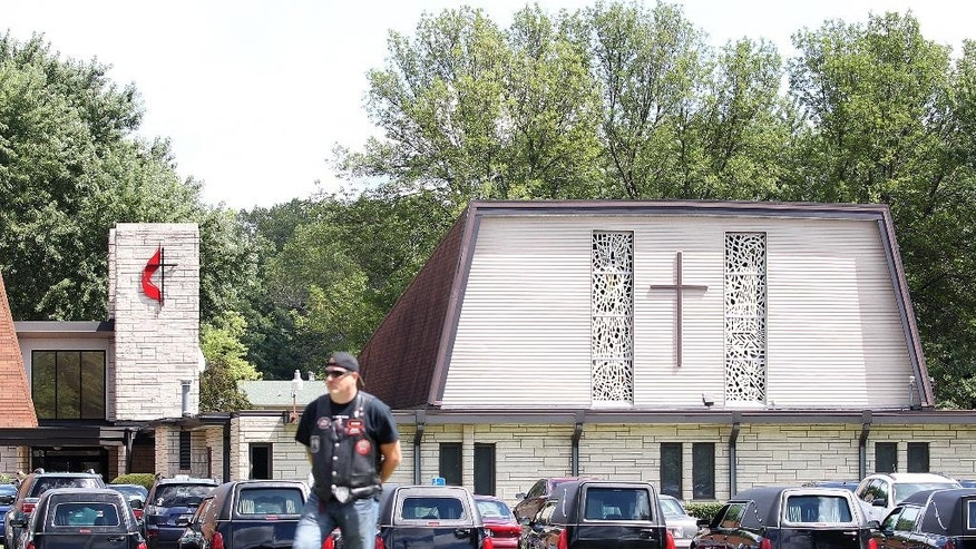 A Bikers Against Child Abuse member stands watch in front of United Method Church in La Crescent, Minn., on Thursday, Aug. 20, 2015, during a funeral service for the eight victims of the Aug. 8, shooting in Houston, Texas. BACA members protected survivors' privacy during the funeral and subsequent burial at Prince of Peace Cemetery. David Conley faces capital murder charges for the killings. Authorities say he handcuffed most of the family members and eventually shot each in the head. (Rory O'Driscoll/La Crosse Tribune via AP) MANDATORY CREDIT