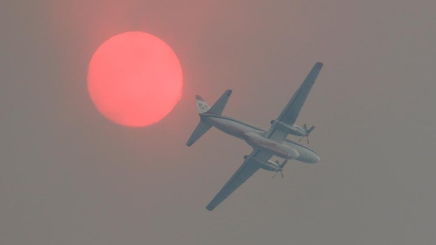 A fire-retardant airplane passes near the sun turned orange with smoke as a wildfire burns near Twisp, Wash. Wednesday, Aug. 19, 2015. (AP Photo/Ted S. Warren)