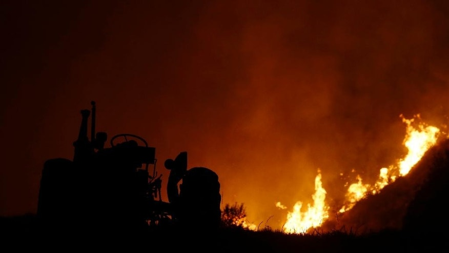 A wildfire burns near a tractor outside of Twisp, Wash., Wednesday, Aug. 19, 2015. Authorities on Wednesday afternoon urged people in the north-central Washington town to evacuate because of a fast-moving wildfire. (AP Photo/Ted S. Warren)