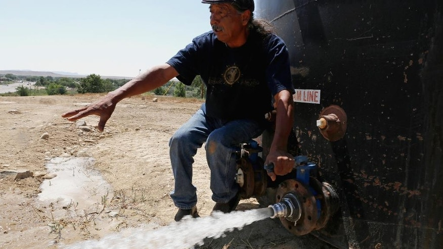 In this Aug. 18, 2015 photo, Joe Ben Jr., Shiprock Chapter House Farm Board representative, tests the water from tanks at the Chief Hill location in Shiprock, N.M. The quality of San Juan River water on the Navajo Nation has returned to what it was before a spill at a Colorado gold mine sent toxic sludge into the waterway, federal officials said Thursday. (Alexa Rogals/The Daily Times via AP) MANDATORY CREDIT