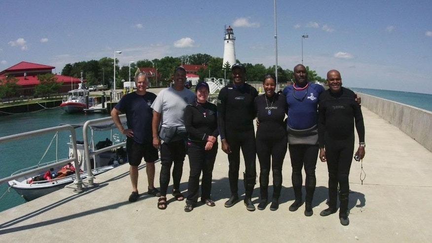 In this Aug. 13, 2015, photo, members of a dive team from left, Wayne Lusardi, Erik Denson, Stephanie Gandulla, Kamau Sadiki, Melody Garrett, Jay Haigler and Ernie Franklin pose for a photo in Port Huron, Mich. The seven spent a week archaeologically documenting for the first time the wreckage of a plane that was piloted by a member of the Tuskegee Airmen. (AP Photo/Mike Householder)
