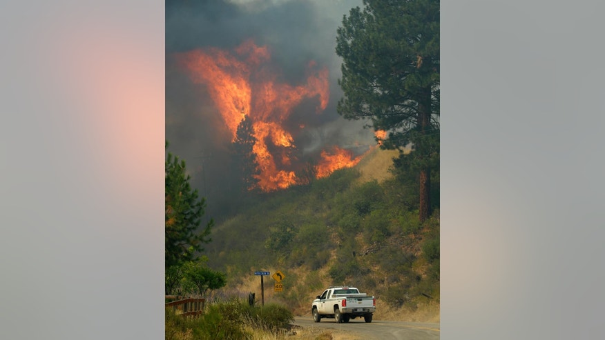 A U.S. Forest Service truck drives near large flames on a hillside along Twisp River Road in Twisp, Wash., Thursday, Aug. 20, 2015. (AP Photo/Ted S. Warren)