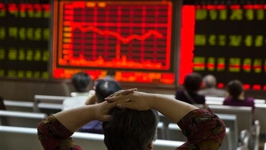 An investor watches a display of stock prices at a brokerage in Beijing, Friday, Aug. 21, 2015.  Asian stocks fell further Friday after a survey showed Chinese manufacturing weakened this month. (AP Photo/Ng Han Guan)