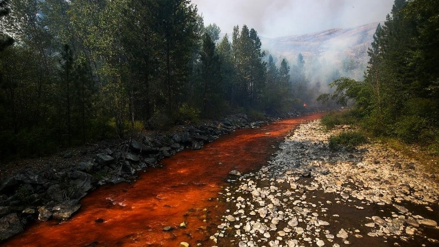 The Twisp River is turned a deep red after an aerial drop of fire retardant landed in the river as a fire flared up near Twisp, Wash., Thursday, Aug. 20, 2015. Authorities warned that more high winds Thursday could make conditions very challenging. (Joshua Trujillo/seattlepi.com via AP) MAGS OUT; NO SALES; SEATTLE TIMES OUT; TV OUT; MANDATORY CREDIT; SEATTLE OUT