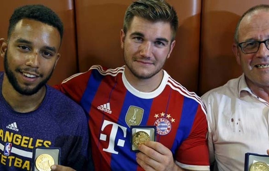 Three men who helped to disarm an attacker on a train from Amsterdam to France, Anthony Sadler, from Pittsburg, California, Aleck Sharlatos from Roseburg, Oregon, and Chris Norman, a British man living in France, pose with medals they received for their bravery at a restaurant in Arras.