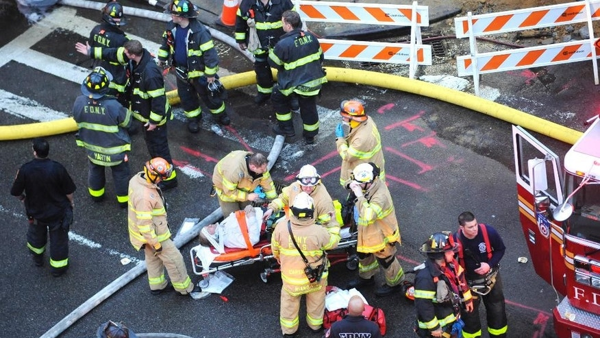 FILE - In this March 26, 2015 file photos firefighters work at the scene of a collapsed building in the East Village neighborhood of New York. At 150 years old, the nation's largest fire department is undergoing a massive shift in hiring and recruitment after a court ordered changes to diversity the almost all-white, all-male  department. (AP Photo/Louis Lanzano, File)