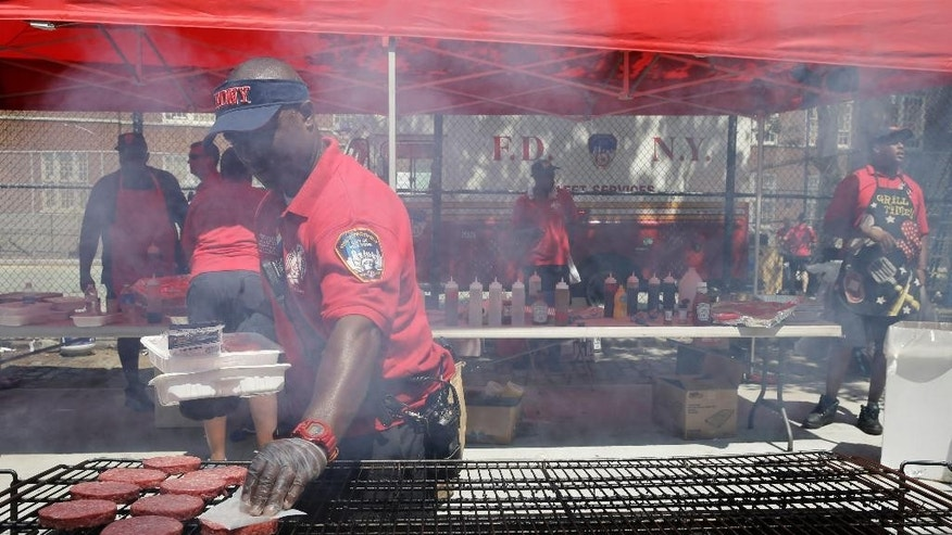 In this Saturday, Aug. 15, 2015 photo, firefighter Khalid Baylor of Truck 14 grills hamburgers during a FDNY block party in the Harlem neighborhood of New York. The block party honored the 150-year history of the nation's largest fire department. Also, a recruitment table was there to help shape a changing future. Three years into a process that has changed recruitment, testing and hiring, the Fire Department of New York is making headway, statistics show.  (AP Photo/Mary Altaffer)