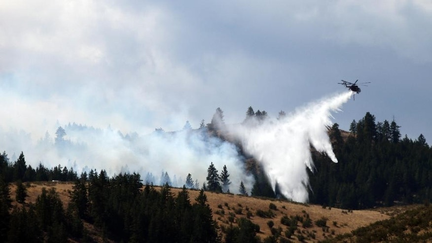 Flames from a wildfire rise atop a hillside near homes below Friday, Aug. 21, 2015, in Tonasket, Wash. The flames were knocked-down within minutes by a firefighting helicopter dropping water. Wildfires picked up their destructive pace across the drought-choked West on Friday, leading residents to flee their homes and authorities to scramble for resources to beat back the flames. (AP Photo/Elaine Thompson)