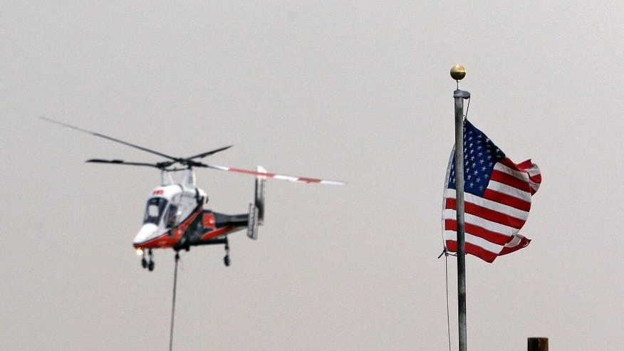 "A firefighting helicopter fills its bucket in view of a United States flag while making runs dumping water on flames threatening homes nearby Friday, Aug. 21, 2015, in Tonasket, Wash. Out-of-control blazes in the north-central part of the state have destroyed buildings, but the situation is so chaotic that authorities have ""no idea"" how many homes may have been lost. (AP Photo/Elaine Thompson)"