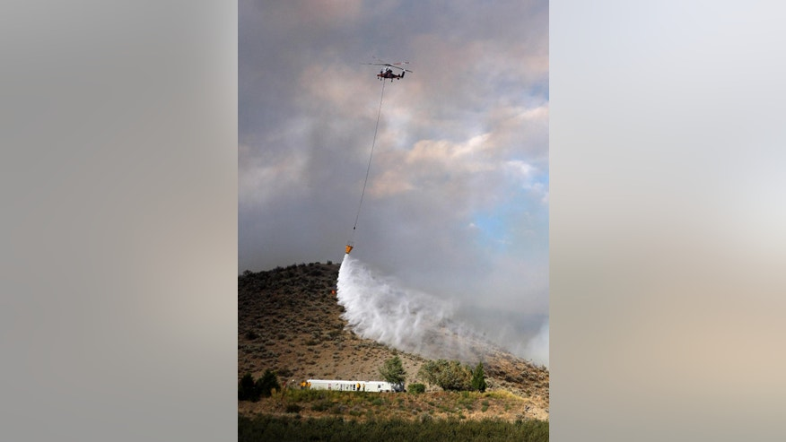 "A firefighting helicopter drops water on flames near a home Friday, Aug. 21, 2015, in Tonasket, Wash. Out-of-control blazes in the north-central part of the state have destroyed buildings, but the situation is so chaotic that authorities have ""no idea"" how many homes may have been lost. (AP Photo/Elaine Thompson)"