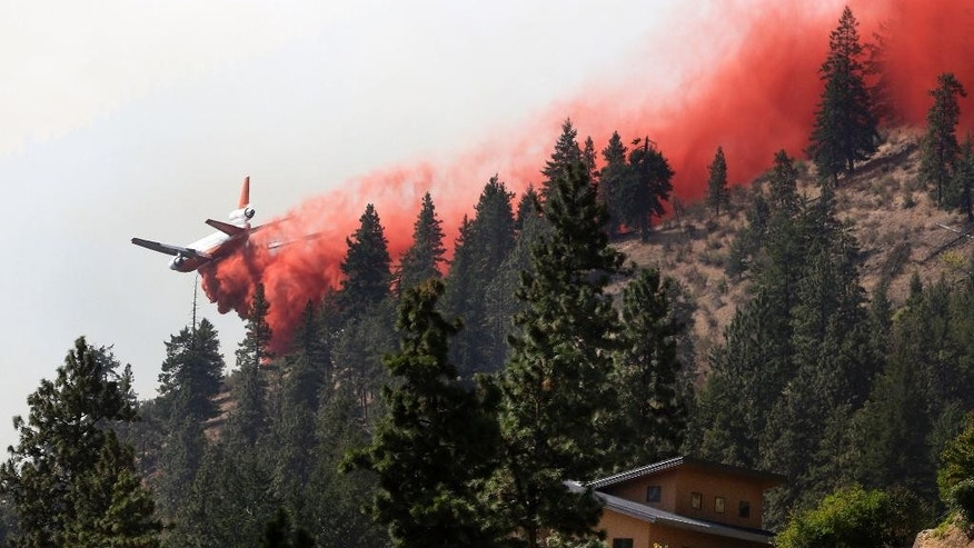 A tanker airplane drops fire retardant on a hillside above a neighborhood on Lake Chelan in north-central Washington state as a wildfire blazes, Friday morning, Aug. 21, 2015. Massive wildfires expanding across the arid state have so overtaxed firefighters that the federal government declared an emergency and state officials took the unprecedented step of seeking volunteers to help fight the flames. (Genna Martin/The Herald via AP) MANDATORY CREDIT