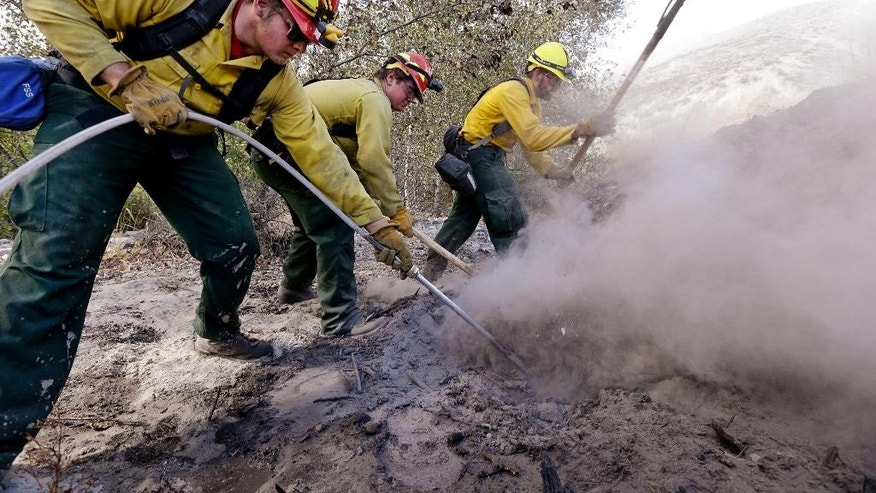 "Novice firefighters Nathan Wilson, left, Ryan Christensen and Jesse Squibb, of Spokane Valley (Wash.) Tech work to put out a hot spot remaining from a wildfire Friday, Aug. 21, 2015, in Tonasket, Wash. Out-of-control blazes in north-central Washington have destroyed buildings, but the situation is so chaotic that authorities have ""no idea"" how many homes may have been lost. (AP Photo/Elaine Thompson)"