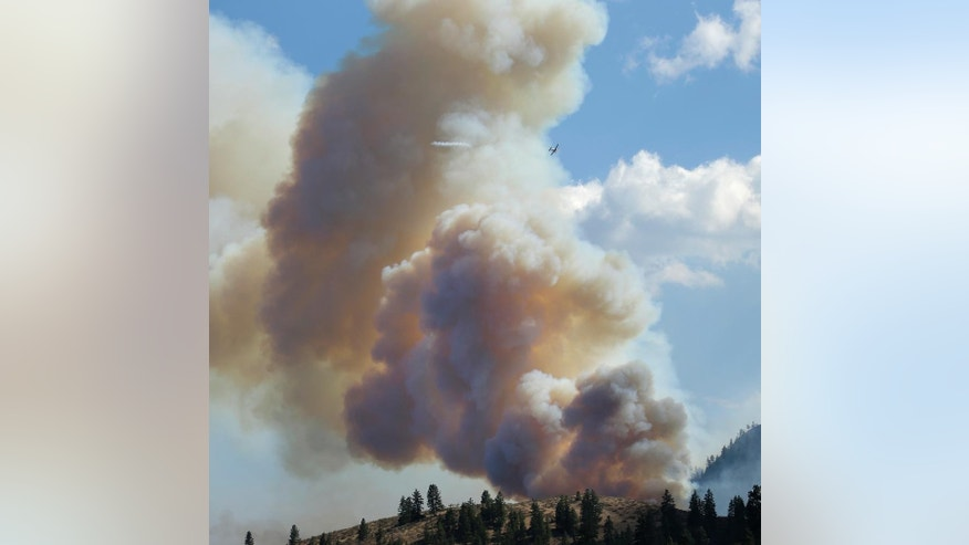 A spotter plane leaves a test line of smoke in front of a massive cloud of smoke as it leads a larger fire retardant tanker plane over a wildfire burning in Twisp, Wash. Friday, Aug. 21, 2015, during an afternoon flare-up. Massive wildfires expanding across the arid state have so overtaxed firefighters that the federal government declared an emergency and state officials took the unprecedented step of seeking volunteers to help fight the flames. (AP Photo/Ted S. Warren)