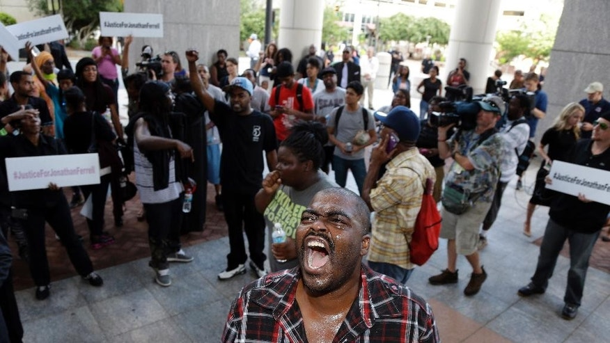 "Protester Derek Strother shouts with others outside of the Mecklenburg courthouse after a mistrial was declared in Charlotte-Mecklenburg Police Officer Randall ""Wes"" Kerrick's trial, Friday, Aug. 21, 2015, in Charlotte, N.C. Kerrick was charged with voluntary manslaughter in the shooting of unarmed African American, Jonathan Ferrell in Sept. 2013. (AP Photo/Bob Leverone)"