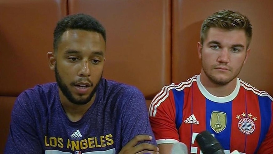 In this image made from TV, Anthony Sadler, a senior at Sacramento State University, left, sits with Alek Skarlatos, US National Guardsman from Roseburg, Oregon, who both helped overpower high-speed train attacker, talk to the media early Saturday Aug. 22, 2015, in Arras, France.  Three Americans and a Briton are together being hailed as heroes for tackling and disarming a gunman aboard a high-speed train traveling between Amsterdam and Paris Friday evening. (AP Photo /APTN) TV OUT - FRANCE OUT