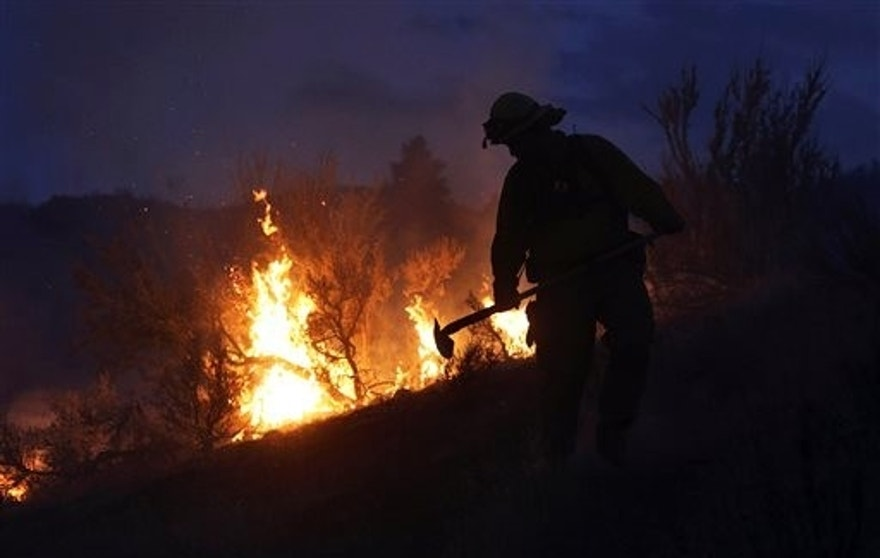 Gold Bar Fire Lt. Scott Coulson investigates brush fires in the hills outside of Omak, Wash., on Friday, Aug. 21, 2015, as wildfires continue to burn throughout north-central Washington. (Genna Martin/The Herald via AP)