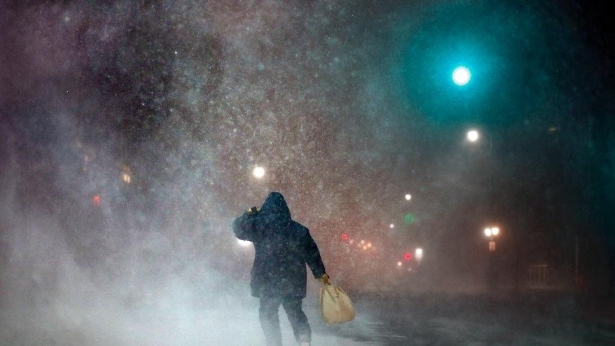 """FILE- In a Tuesday, Jan 27, 2015 file photo, a man battles fierce headwinds as he walks on Congress Street in Portland, Maine, during a blizzard. The editors of the Maine-based Farmers' Almanac have dubbed their latest forecast a """"winter deja vu,"""" hearkening to last winter's misery across the Northeast (AP Photo/Robert F. Bukaty)"""