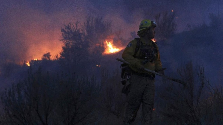 In this photo taken on Friday night, Aug. 21, 2015, Gold Bar fire Lt. Scott Coulson keeps an eye on a wildfire in the hills outside of Omak, Wash., as wildfires continue to burn throughout north-central Washington. (Genna Martin/The Herald via AP) MANDATORY CREDIT