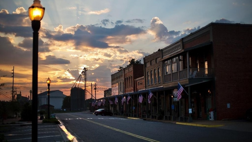 The sun rises behind Main Street in the hometown of former President Jimmy Carter in Plains, Ga., Sunday, Aug. 23, 2015. Carter and his hometown have always been intertwined, from the day he announced he would run for president and an old train depot downtown became a local campaign office. He and his wife, Rosalynn, have always kept a home there, but the 90-year-old Carter intends to spend a lot more time in the tiny town as he's treated for cancer that has spread to his brain. (AP Photo/David Goldman)
