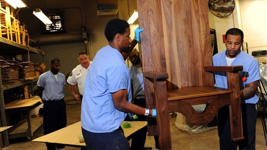 Inmates Rameen Perrin, left, and Evan Davis working a chair carved out of walnut for Pope Francis to use during his planned visit to the prison next month, Monday, Aug. 24, 2015, at the  Curran-Fromhold Correctional Facility in Philadelphia. Francis plans to meet on Sept. 27 with about 100 inmates and some of their relatives during a two-day trip to the city. (AP Photo/Michael Perez)