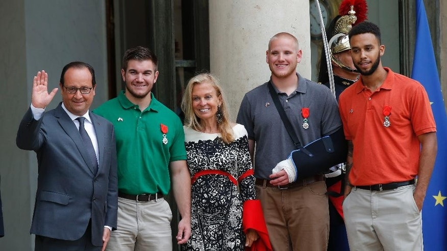 CORRECTS SADLER'S SCHOOL TO SACRAMENTO STATE UNIVERSITY, INSTEAD OF SACRAMENTO UNIVERSITY - From left, French President Francois Hollande, U.S. National Guardsman from Roseburg, Ore., Alek Skarlatos, U.S. Ambassador to France Jane D. Hartley, U.S. Airman Spencer Stone and Anthony Sadler, a senior at Sacramento State University in California, pose for photographers as they leave the Elysee Palace in Paris, France, after Hollande awarded the three men with the French Legion of Honor on Monday, Aug. 24, 2015. The three American travelers say they relied on gut instinct and a close bond forged over years of friendship as they took down a heavily armed man on a passenger train speeding through Belgium on Friday, Aug. 21. (AP Photo/Michel Euler)