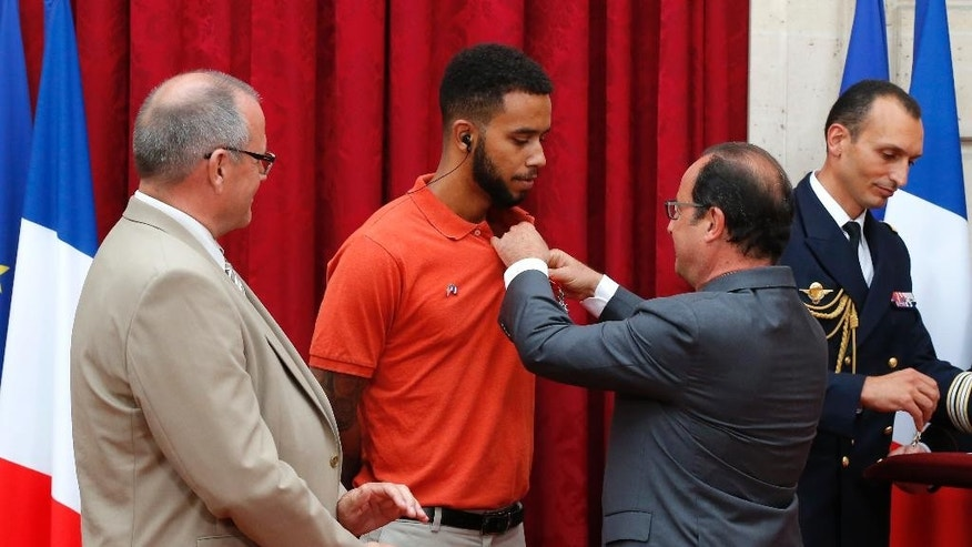 CORRECTS SADLER'S SCHOOL TO SACRAMENTO STATE UNIVERSITY, INSTEAD OF SACRAMENTO UNIVERSITY - French President Francois Hollande, right, attaches the Legion of Honor award to the shirt of Anthony Sadler, a senior at Sacramento State University in California, as British businessman Chris Norman, left, looks on at the Elysee Palace, Monday Aug. 24, 2015 in Paris, France. Hollande also presented the award to Sadler's years-long friends U.S. Airman Spencer Stone and National Guardsman Alek Skarlatos. The three took down a heavily armed man Friday, Aug. 21, on a passenger train speeding through Belgium. Norman also jumped into the fray. (AP Photo/Michel Euler, Pool)