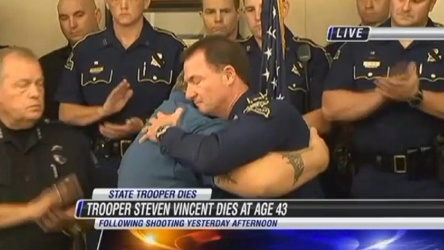 In this frame from video provided by KPLC, state police chief Mike Edmonson, right, embraces with Robert Ledoux, the good Samaritan who helped capture a man accused of shooting a state trooper, Monday, Aug. 24, 2015, in Lake Charles, La. Kevin Daigle is accused of shooting Senior Trooper Steven Vincent on Sunday evening when Vincent found Daigle's truck in a ditch. (KPLC via AP) MANDATORY CREDIT; LOCAL MEDIA OUT; AMERICAN PRESS OUT
