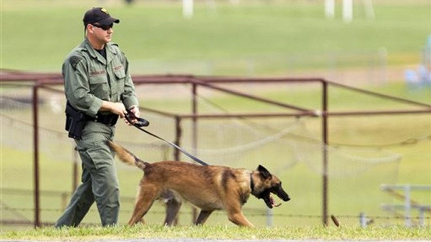 Aug. 25, 2015: A West Virginia Police officer and a dog walk around the perimeter of Philip Barbour High School grounds following a hostage in Philippi, W.Va.