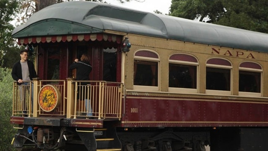 FILE - In this June 2, 2011 file photo, a couple takes pictures at the back of the Napa Valley Wine Train as it makes its way through St. Helena, Calif. (AP Photo/Eric Risberg, File)