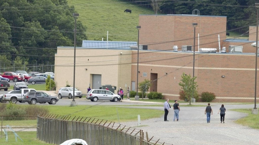 "Parents of children from Philip Barbour High School in Philippi, W.v.,walk to the school to meet up with their children that were evacuated after a ""hostage-like"" situation occurred in the cafeteria of the school, Tuesday, Aug. 25, 2015. State Police spokesman Lt. Michael Baylous says a suspect was taken into custody Tuesday afternoon at Philip Barbour High School. No injuries were reported. (AP Photo/Ben Queen)"