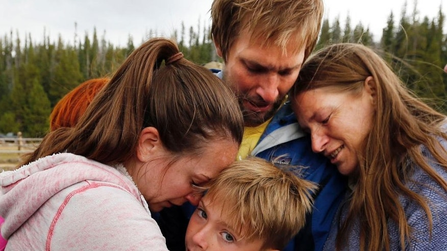 Malachi Bradley, center, is reunited with his family, Monday, Aug. 24, 2015, in Uintah County, Utah, after being lost near a remote mountain lake near the Wyoming border on Sunday. Also pictured are his mother, Molly Chrisman, left, father, Danny Bradley, top, and grandmother Sharon Clark. (Ravell Call/The Deseret News via AP)  SALT LAKE TRIBUNE OUT; MAGS OUT; MANDATORY CREDIT